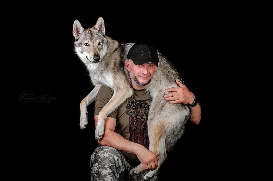 Человек несет волка на руках
